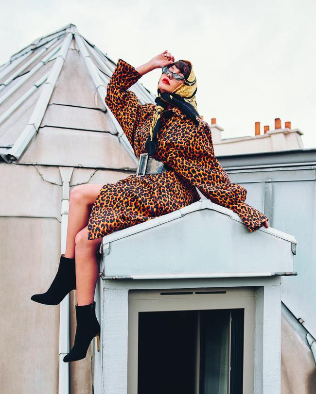المعطف من  Yves Saint Laurent والنظّارات من  Poppy Lissiman والحزام من  Alexandre Vauthier والحذاء من  Bettina Vermillon