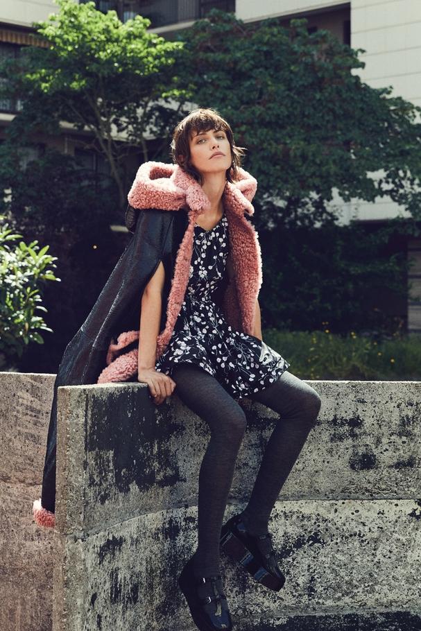 """رداء بقلنسوة مصنوع من جلد الغنم وفستان من نسيج التفتة الحريريّ وجوارب وحذاء """"platform"""". كلّها من Miu Miu"""