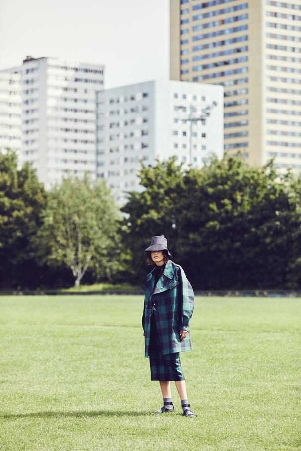 معطف واقٍ من المطر مصنوع من القطن والبوليستر وبوديسوت من الصوف المحبوك وتنّورة ضيّقة من الصوف الرقيق وقبعة وصندل. كلّها من Christian Diorوجوارب من  Doré Doré