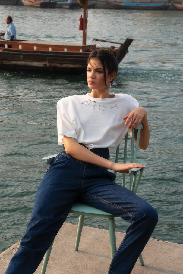 قميص تي شيرت من Alessandra Rich لدى Harvey Nichols دبي وجينز من Attico لدى Harvey Nichols دبي وأقراط من  Georg Jensenوأقراط ملتصقة وخاتم من  Repossi
