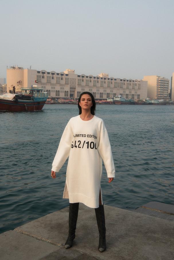 الفستان الصوفيّ من Maison Margiela لدى Harvey Nichols دبي ومجوهرات من  Repossiوالجزمة من  Jimmy Choo