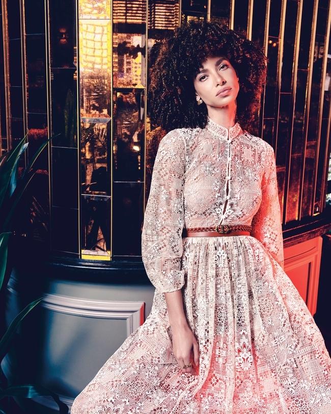 فستان باللون الأبيض الفاتح وحزام DiorDouble باللون البني وأقراط وخاتم.كلّها من Dior