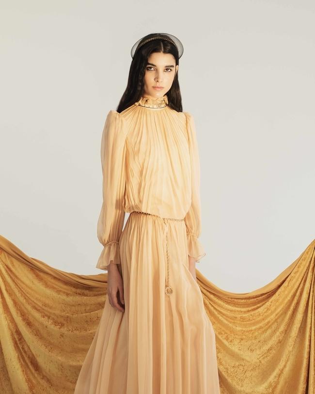 فستان من Alberta Ferretti وحزام من Giuliana Mancinelli Bonafaccia وعقد من Barbara Biffoli وإكسسوار للشعر من The Beatriz